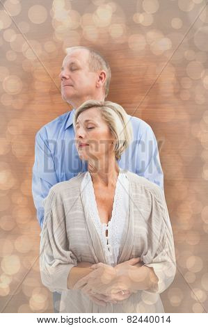 Happy mature couple embracing with eyes closed against light glowing dots design pattern