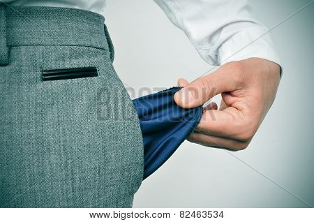 a broke businessman showing his empty pocket