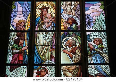 KUTNA HORA, CZECH REPUBLIC - AUGUST 23, 2014: Luke the Evangelist painting the Virgin Mary. Art Nouveau stained glass window in Saint Barbara Church in Kutna Hora, Czech Republic.