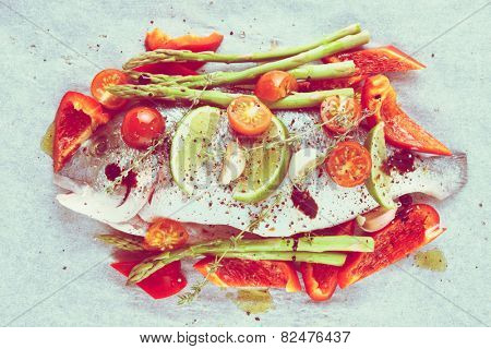 Dorade with vegetables prepared for roasting in culinary paper bag, toned image