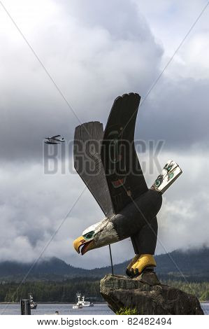 Wooden Bald Eagle statue in Ketchikan with float plane in sky