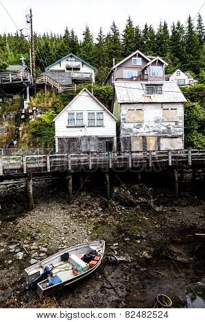 Weathered houses on banks of Tongass Narrows at Ketchikan with moored boat