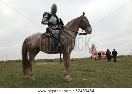 MILOVICE, CZECH REPUBLIC - OCTOBER 23, 2013: Actor dressed as a medieval knight rides a horse during the filming of the new movie The Knights near Milovice, Czech Republic.