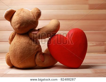 Teddy Bear with red heart on wooden background