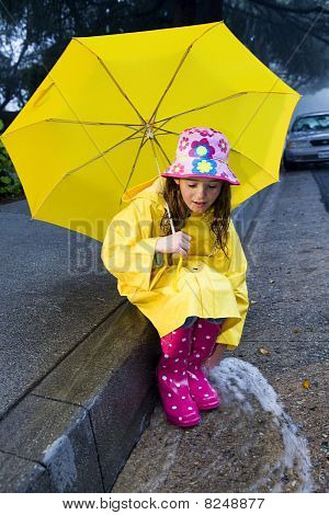 Young girl playing in rain with umbrella 2