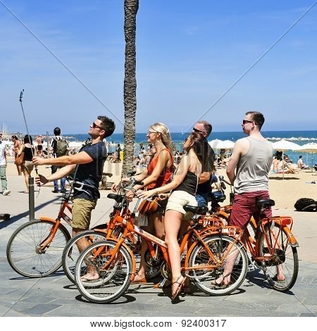 BARCELONA, SPAIN - MAY 28: A group of tourists riding a bicycle take a selfie with a monopod in the seafront of La Barceloneta Beach on May 28, 2015 in Barcelona, Spain