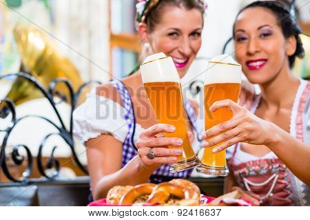 Women in Bavarian pub wearing traditional Tracht toasting with wheat beer