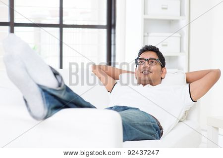 Indian guy daydreaming and rest at home. Asian man relaxed and lying on sofa indoor. Handsome male model.