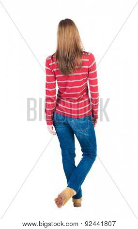 back view of standing young beautiful  blonde woman in jeans. girl  watching. Rear view people collection.  Isolated over white background. Throwing his legs blonde in striped red sweater looks ahead