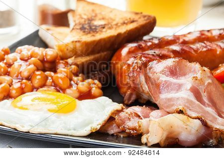 Full English Breakfast With Bacon, Sausage, Egg, Baked Beans And Orange Juice