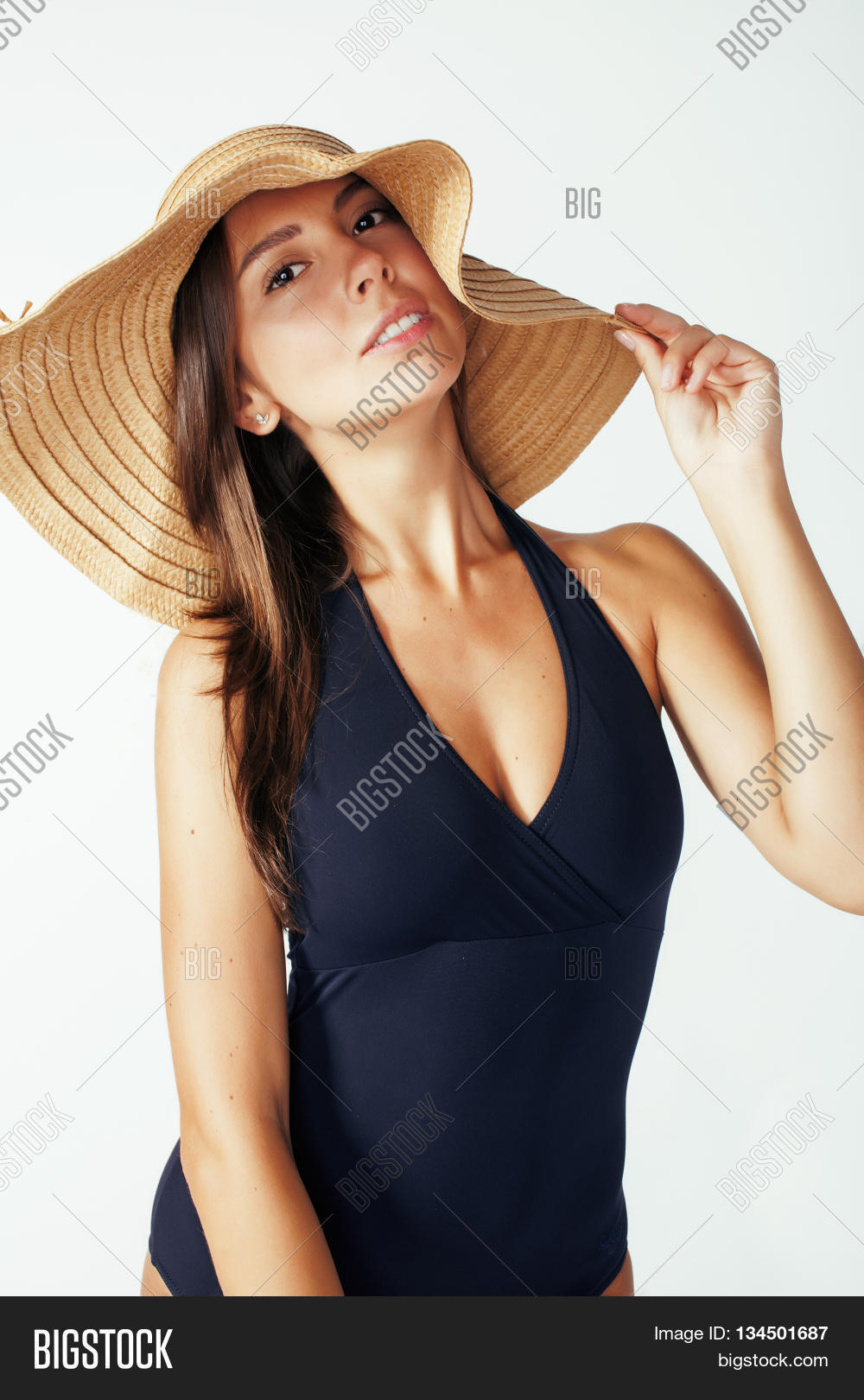 50851232 young pretty brunette woman wearing summer hat and swimsuit isolated on  white background preparing to vacations