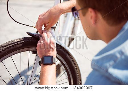 I have to do it. Young man with sunglasses repairing attentively a handbrake on his bicycle