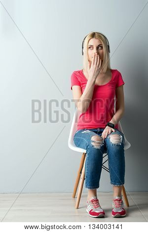 Portrait of cute blond girl listening to music from headphones. She is sitting on chair. The lady is coveting mouth by palm and looking aside with surprise. Copy space in left side