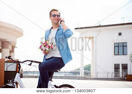 Waiting for you. Contended smiling young man talking on the phone while sitting on the bike and holding flowers
