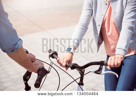 Lets go. Picture of hands of a man and a woman holding handels of their bikes while having a conversation