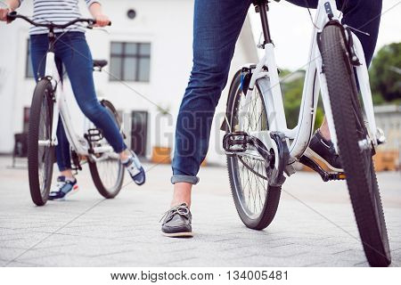 We are ready. Legs of a man and a woman standing with bicycles ready for riding in the city