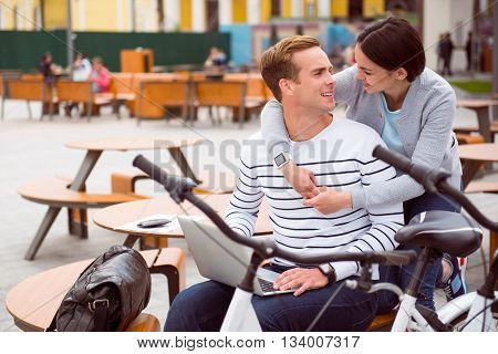 Time together. Contended young woman hugging a relaxed man with a laptop and looking at him after a walk on bikes