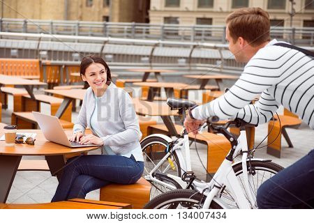 What a chance encounter. Delighted confident young woman sitting and using a laptop while looking at a man sitting on a bike