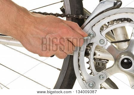 Man fixing chainring on a bicycle on white background - bike repair concept