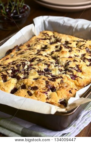 Cherry blondie or blond brownie cake baked with white and dark chocolate photographed in baking pan with natural light (Selective Focus Focus one third into the cake)
