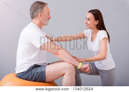 Sporty lifestyle. Delighted senior male patient sitting on a gym ball with dumbbells during physical therapy praxis and smiling female physiotherapist exercising with him being on a grey background