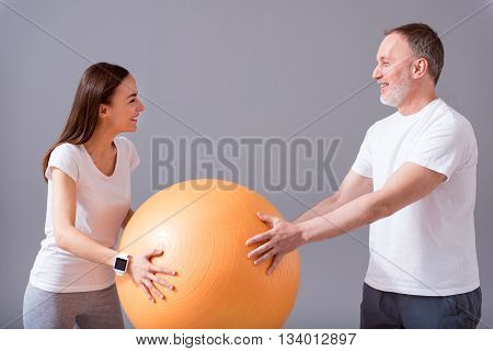 Orange equipment. Cheerful senior male patient exercising with a help of smiling female physiotherapist holding an orange gym ball while standing on isolated grey background