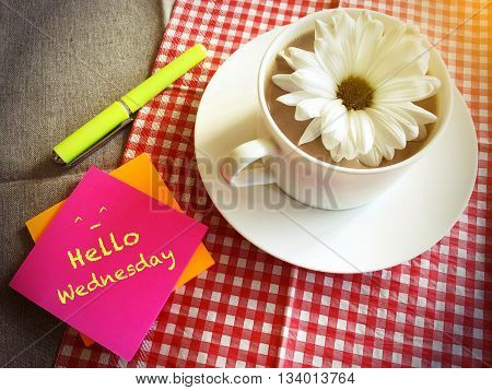 coffee cup on table with white daisy and words Hello Wednesday vintage style