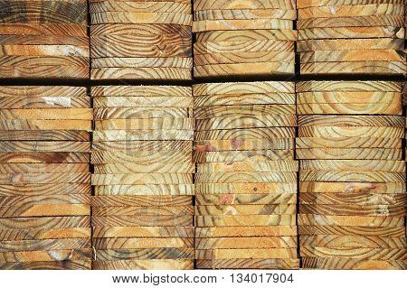 neatly stacked wood beam with texture and cross section as construction material