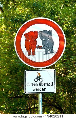 SCHWALBACH, GERMANY - JUL 9, 2012: sign forbidden for elefants in love and bicycle overtaking allowed as fun sign