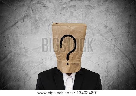 Businessman with brown paper bag on head, with question mark, on concrete texture background