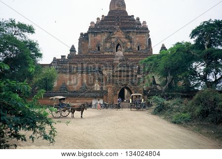 PAGAN BURMA (NOW CALLED MYANMAR) - CIRCA 1987: A horse-drawn carriage waits outside the entrance to the ancient Htilominlo Temple in Pagan.