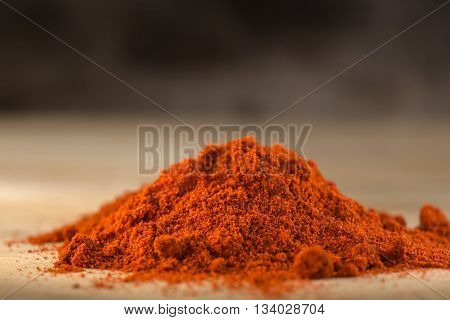 Red hot paprika powder heap on wooden background