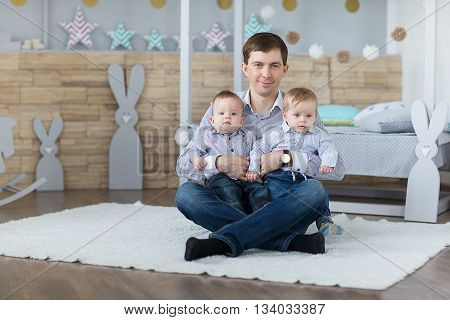 Portrait of dad with twin boys in the nursery.