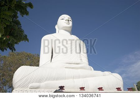 KANDY, SRI LANKA - MARCH 17, 2015: Giant seated Buddha statue in the Mahabodhi temple Sri Maha Viharay. Religious landmark of the city Kandy, Sri Lanka
