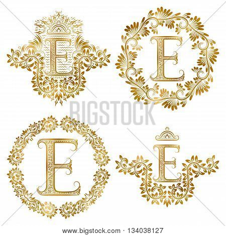 Golden letter E vintage monograms set. Heraldic monogram in coats of arms form letter E in floral round frame letter E in wreath heraldic monogram in floral decoration with crown.