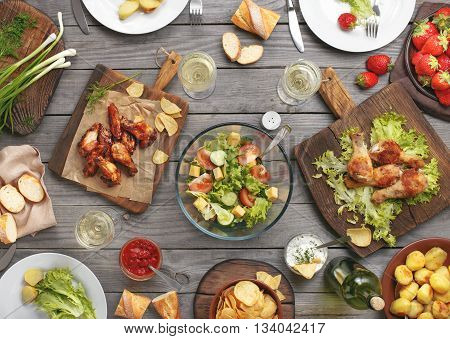 Different food cooked on the grill on a wooden table grilled chicken legs buffalo wings salad potatoes bottle of wine and three glasses of wine and strawberry. Outdoors Food Concept