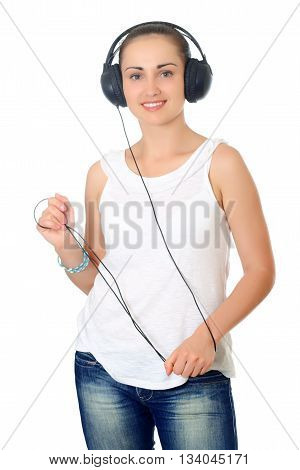 young woman with dark hair standing posing with headphones. Half-lenght portrait on white background, isolated