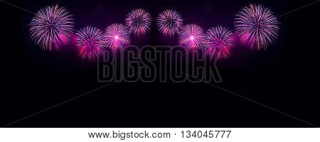 Pink and purple fireworks in the night sky