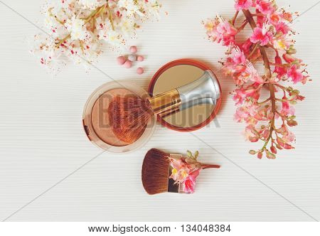 There White and Pink  Branches of Chestnut Tree,Bronze Powder with Mirror and Two Make Up Brushes are on White Table,Top View