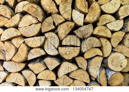 Firewood texture background. Chopped birch firewood, stacked in woodshed and snowbound