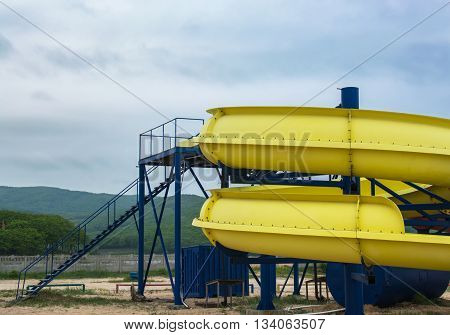 Staircase to the top of a yellow waterslide on the seaside