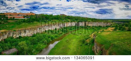 green summer hills in canyon of Dnister river in Ukraine with white clouds on blue sky landscape. Kamenets-podolsky. Ukraine