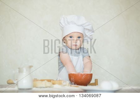 The little boy in a suit of the cook sculpts dough. Baby make dinner in chef suit