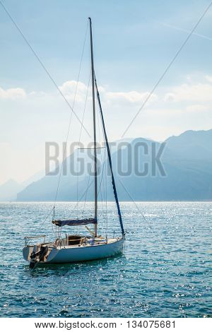 Sailer at water of lake or sea bay and high blue mountains in misty background landscape