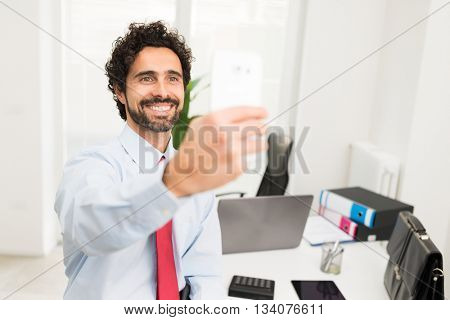 Businessman taking a selfie portrait in his office