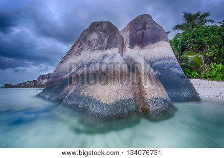 Beautifully shaped granite boulders in the sea of Seychelles at Anse Source d'Argent beach taken with a long exposure. Dramatic stormy sky at sunset time