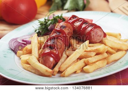 Grilled meat sausage with ketchup and french fries