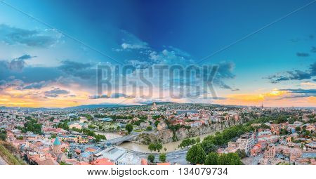 Evening View Of Tbilisi At Colorful Sunset, Georgia. Summer Cityscape. On Panoramic Photograph Visible The Bridge Of Peace, A New Concert Hall, Avlabar Residence - Presidential Administration Of Georgia, Holy Trinity Cathedral Of Tbilisi, Metekhi Church A