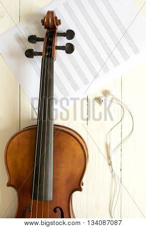 top view of violin and music staff with earphone on white wood background