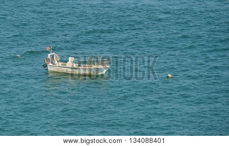 ARMACAO DE PERA PORTUGAL -MAY 18: A view of a small boat moored in the sea of Atlantic ocean near city Armação de Pêra in the south of the country Portugal 2016